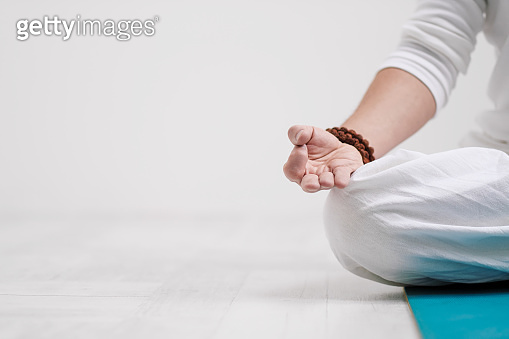 Concept of yoga and meditation. Close-up, hands of a man in white clothes, folded in prayer. White background and yellow-mini rubber mat.
