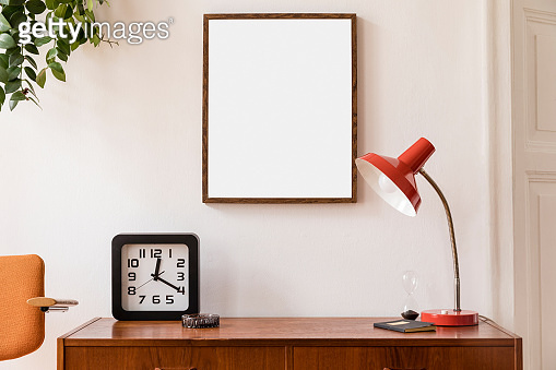 Stylish room of home interior with brown mock up frame with vintage accessories, plant, black clock, chair and red table lamp. Cozy home decor. Minimalistic concept. Retro composition of cupboard.