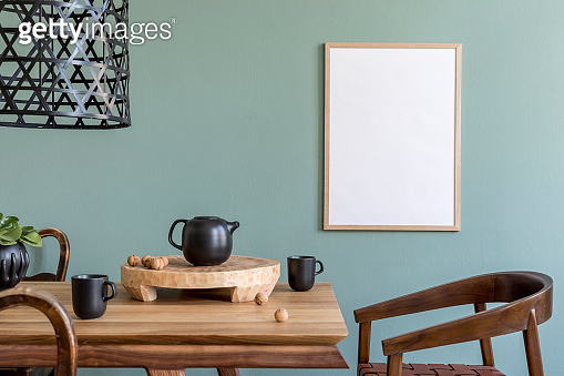 Stylish and design dining room interior with mock up poster frame, wooden table, chairs, teapot with cups, plant, rattan decoration and elegant accessories. Ready to use. Template.