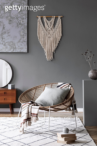 Stylish and boho composition of living room with design armchair, wooden retro commode with mirror, vase with flowers, beige macrame, books and elegant accessories. Modern home decor. Template.