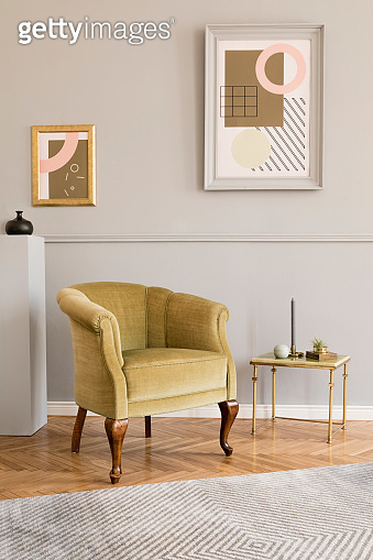 Stylish and luxury living room of apartment interior with elegant green armchair, retro table, gray stand and chic accessories. Mock up paintings frames on the molding gray wall. Nice home decor.