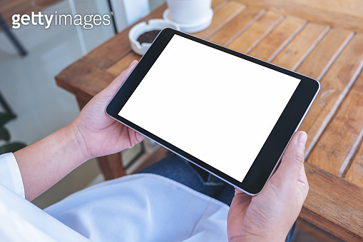 a woman holding black tablet pc with blank white screen