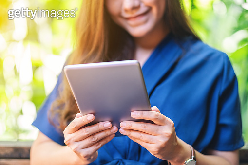 a beautiful woman holding and using tablet pc while sitting in the garden