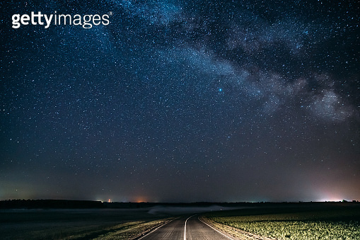 Blue Night Starry Sky Above Country Asphalt Road In Countryside And Green Field. Night View Of Natural Glowing Stars And Milky Way Galaxy