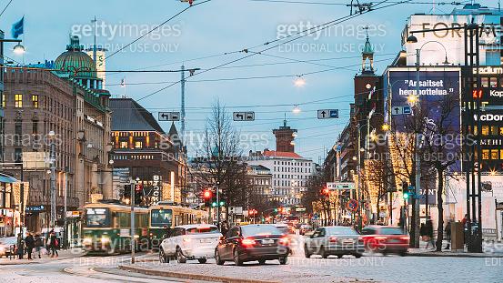 Helsinki, Finland. Tram Departs From A Stop On Street Aleksanterinkatu In Helsinki. Night View Of Aleksanterinkatu Street In Kluuvi District In Evening Or Night Illumination
