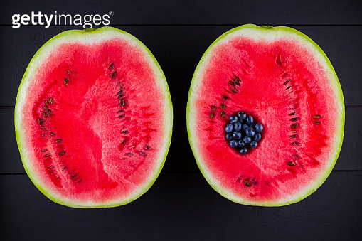 Watermelon and blueberries on dark background. Blueberries in watermelon. Creative food concept. Top view