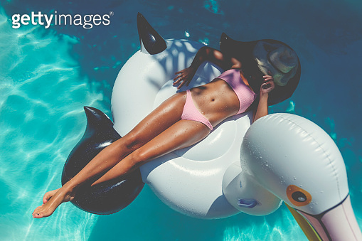 Woman floating on a white inflatable in swimming pool in a pink bikini.