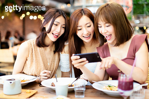 Happy friends having dinner and watching smart phone in  restaurant
