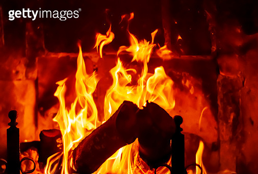 Fire burns in the fireplace powered by wooden logs.