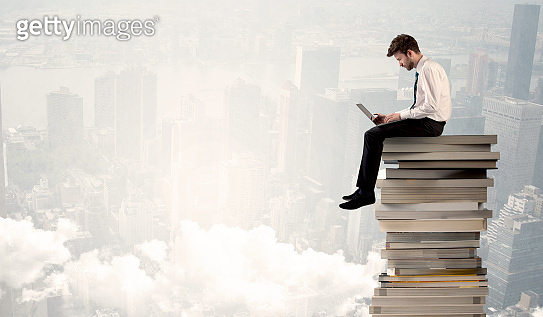 Student in city sitting on stack of books