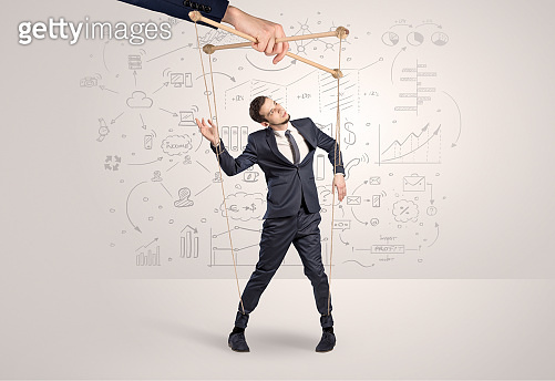 Little businessman controlled from above by another big hand