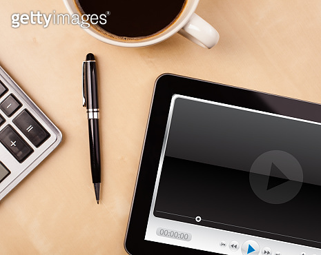 Tablet pc showing media player on screen with a cup of coffee on a desk