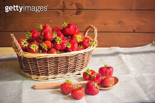 Ripe red strawberries in basket and near on table.