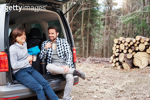 Cheerful boy and his dad drinking tea during spring hiking trip