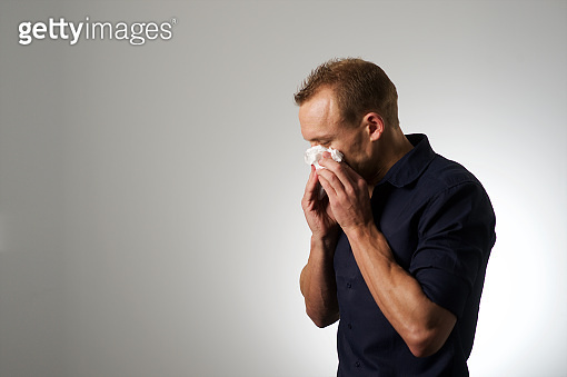 Studio portrait young male with short hair blowing his nose