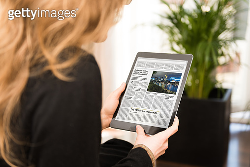 Young woman reading the news on a modern tablet computer