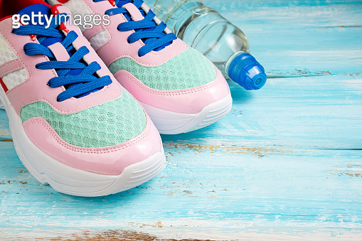 Pink sport shoes and bottle of water on blue wooden background. Sport, healthy lifestyle, slimming, running concept. Trendy female sport equipment