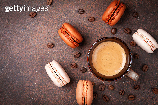 Morning cup of coffee and dessert macaron or macaroon on brown table top view. Flat lay.