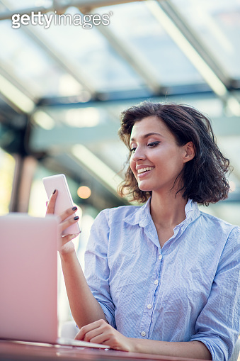 Portrait of a playful young girl taking selfie with mobile phone while sitting with laptop computer at a cafe outdoors