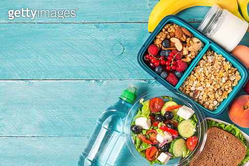 set of lunch boxes with food ready to go for work or school. greek salad, sandwich, vegetables, granola, nuts, berries