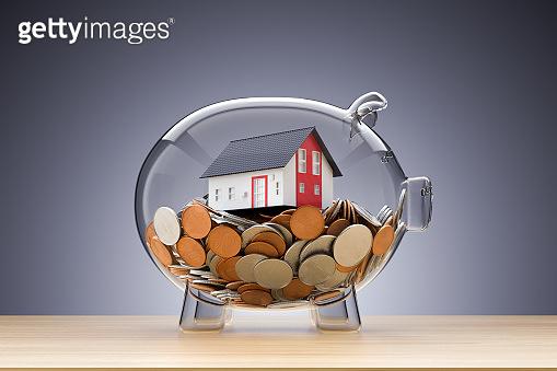 Model House on money inside transparent piggy bank