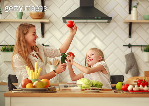 Joyful mother with daughter at home in kitchen having fun playing with food