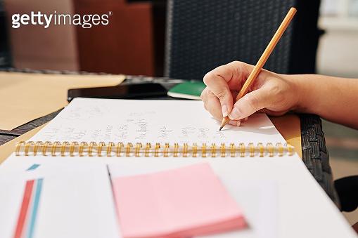 Woman writing in textbook
