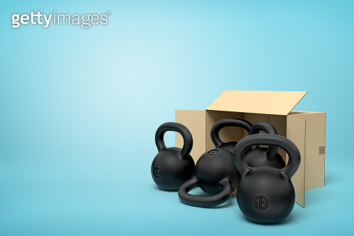3d rendering of several black kettlebells near open cardboard box that is lying sidelong on light-blue background with copy space.
