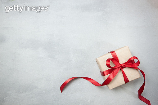 Present or gift box in a craft paper with gold ribbon bow