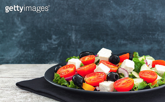 Greek salad of fresh cucumber, tomato, sweet pepper, lettuce, feta cheese and olives with olive oil. Healthy food