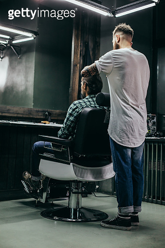 Full length of barber standing behind his client and cutting his hair