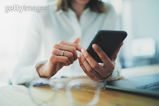 Female hands holding smartphone and touching screen.Businesswoman using mobile phone.Closeup on blurred background.