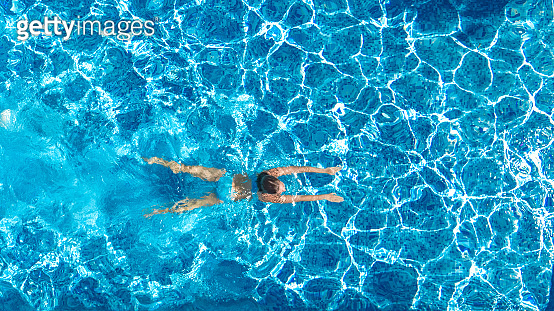 Active girl in swimming pool aerial drone view from above, young woman swims in blue water, tropical vacation, holiday on resort concept
