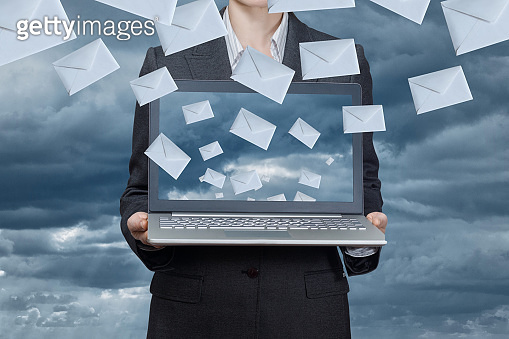 A businesswoman is holding a notebook with envelope icons flying from it.