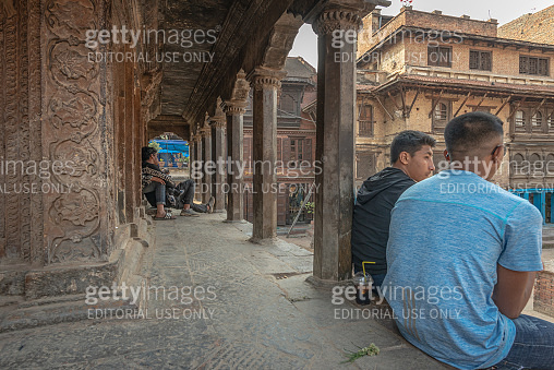 Two young men discussing on the steps of a temple, Patan, Nepal
