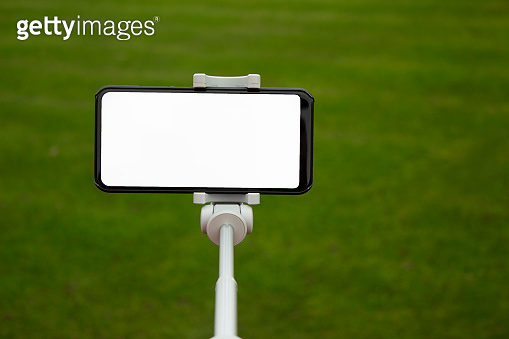 Mock up of a black smartphone with a selfie stick. White screen for the design of the template on the background of a green lawn on the football field.