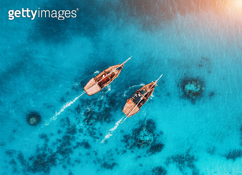 Aerial view of the fishing boats in transparent blue water at sunset in summer. Top view from drone of floating boat in Indian ocean in Zanzibar, Africa. Landscape with yacht in clear sea. Seascape