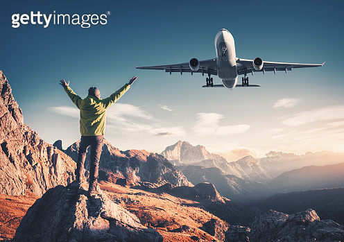 Airplane and man on the stone with raised up arms against mountains at sunset. Happy sporty man, flying passenger airplane, rocks and blue sky in Dolomites, Italy. Traveler and landing aircraft