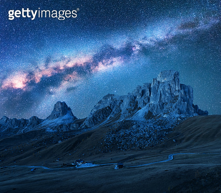 Milky Way above mountains at night in summer. Landscape with alpine mountain valley, road, sky with bright milky way and stars, buildings on the hill, rocks. Passo Giau in Dolomites, Italy. Space
