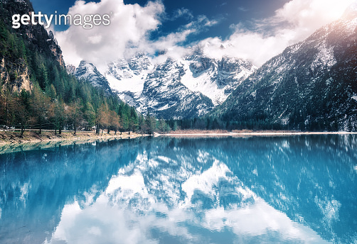 Mountain lake with perfect reflection at sunset in autumn. Dolomites, Italy. Beautiful landscape with azure water, trees, snowy mountains in clouds, blue sky in fall.  Snow covered rocks. Nature