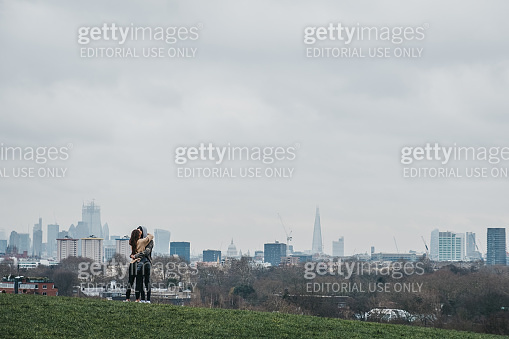 Couple hug on top of Primrose Hill, London, UK, ccity skyline on the background.