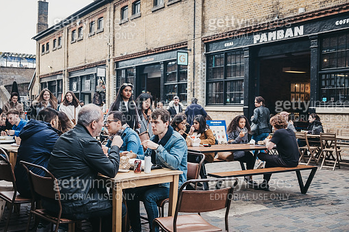 People sitting at outdoor tables inside Camden Market, London, UK.