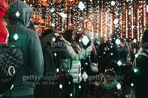 People talking photos inside Winter Lights festival in Canary Wharf, London, UK.