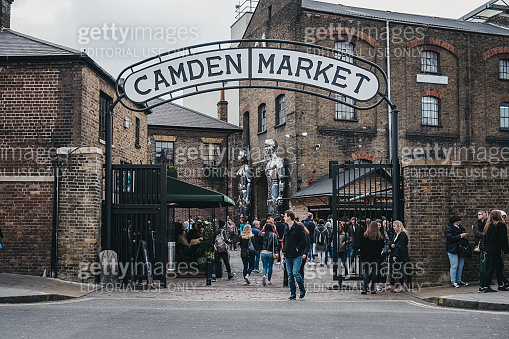 People entering Camden Market, London, UK, through the gates, under a name sign.