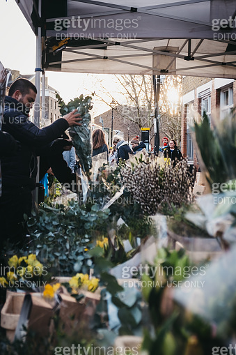 People buying flowers at Columbia Road Flower Market, London, UK.