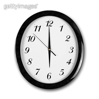 Large round white wall clock with black frame. The hands point to 6 o'clock. Close up. Isolated on white background