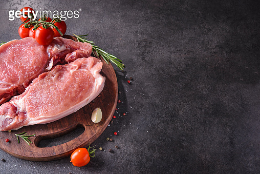 Raw pork steak on a wooden board