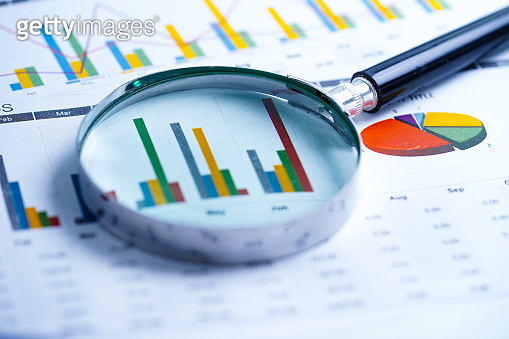 Magnifying glass on charts graphs spreadsheet paper. Financial development, Banking Account, Statistics, Investment Analytic research data economy, Stock exchange trading, Business office company meeting concept.