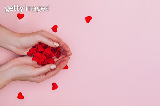 Woman's hands full of small red hearts on pink background. Love, care, affection, the St. Valentine's day concept.