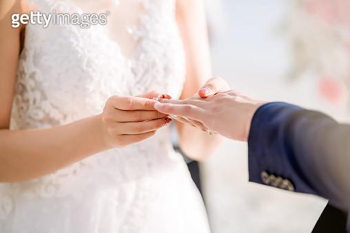 Wedding rings.She Put the Wedding Ring on Him.Close up bride Put the Ring on Groom. Wedding ceremony and wedding decoration.